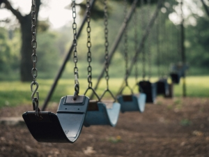 a row of empty park swings